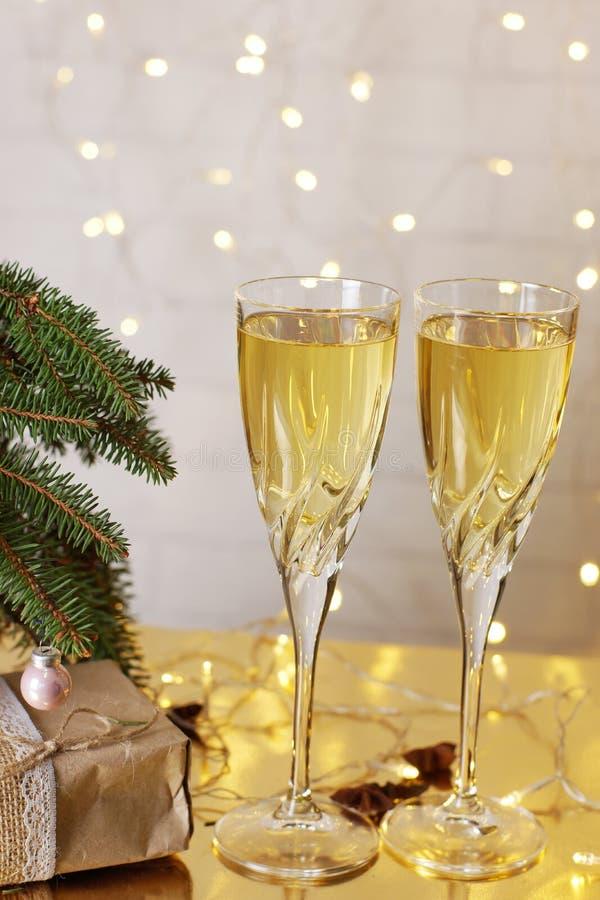 Deux verres de champagne sont sur la table à côté des présents de Noël et de nouvelle année sous l'arbre de Noël photographie stock libre de droits