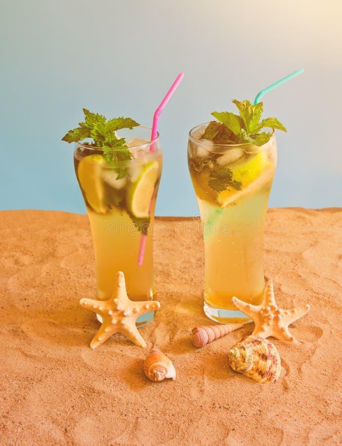 Deux verres de cocktail de mojito avec les pailles ? boire sur la plage de sable sur le contexte bleu photo libre de droits