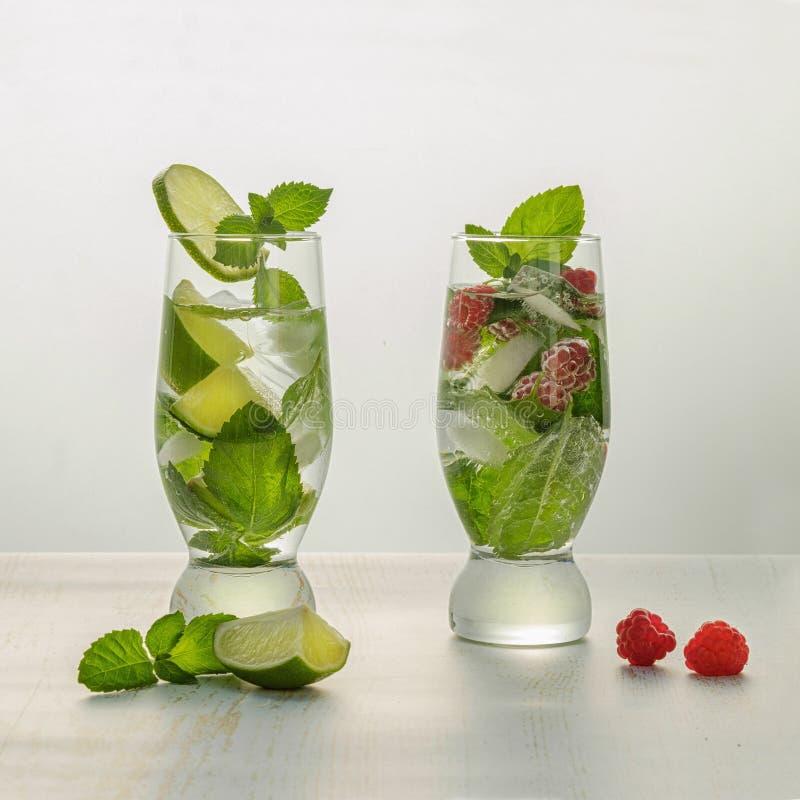 Deux verres de cocktail, de Mojito classique et de Mojito avec des framboises image stock