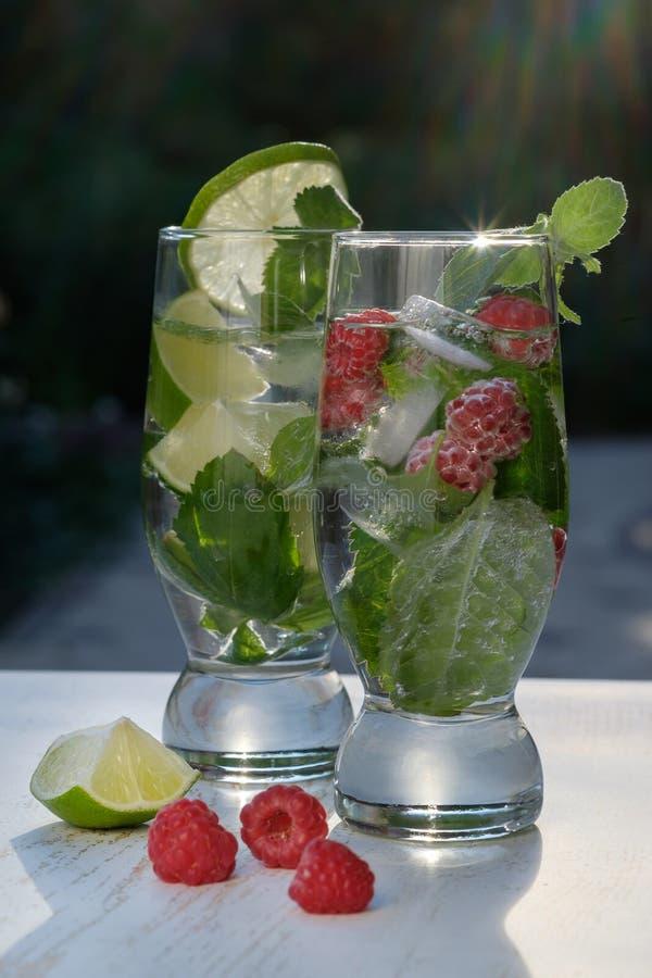 Deux verres de cocktail, de Mojito classique et de framboise Mojito au soleil photos libres de droits