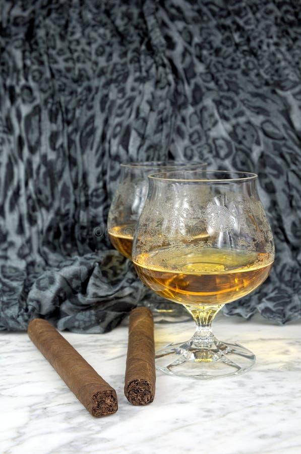 Deux verres de cognac avec un cigare sur une table de marbre images libres de droits