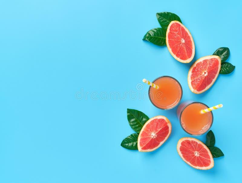 Deux verres de jus de pamplemousse frais sur un fond bleu principal vi photo stock