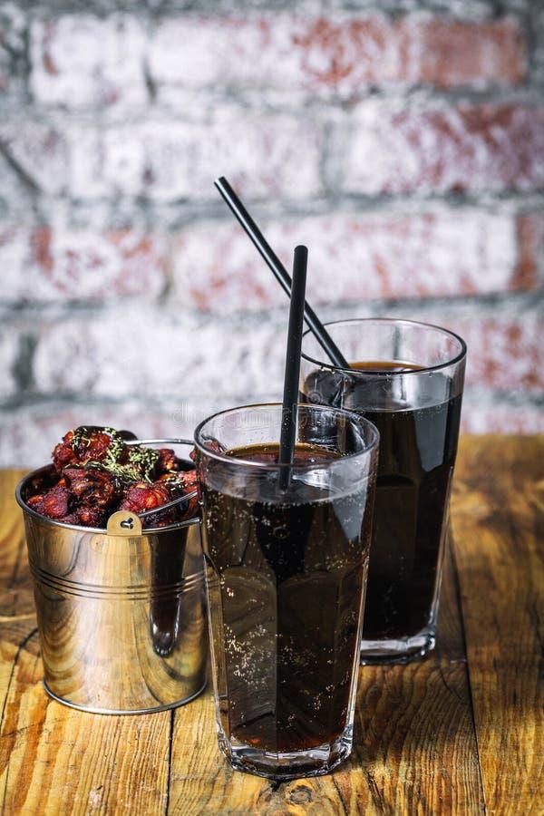 Deux verres de kola et de seau de poulet fryed des ailes photo libre de droits