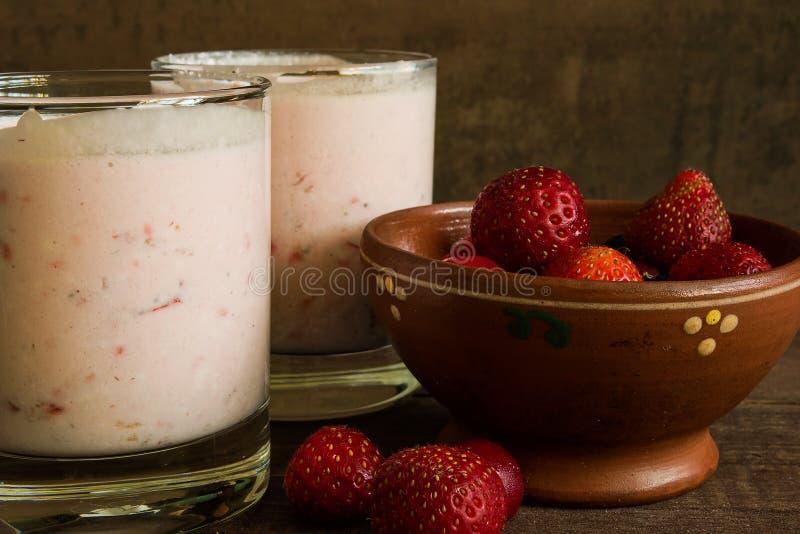 Deux verres de smoothie de baie avec des baies dans le plat de poterie image libre de droits