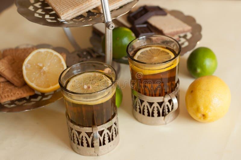 Deux verres de thé noir en supports en verre, quelques bonbons, citrons mûrs et chaux sur une surface de toile sur le fond léger images libres de droits