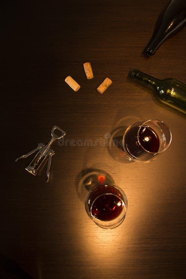 Deux verres de vin avec une bouteille vide, un tire-bouchon et quelques lièges dans des tons foncés photographie stock libre de droits