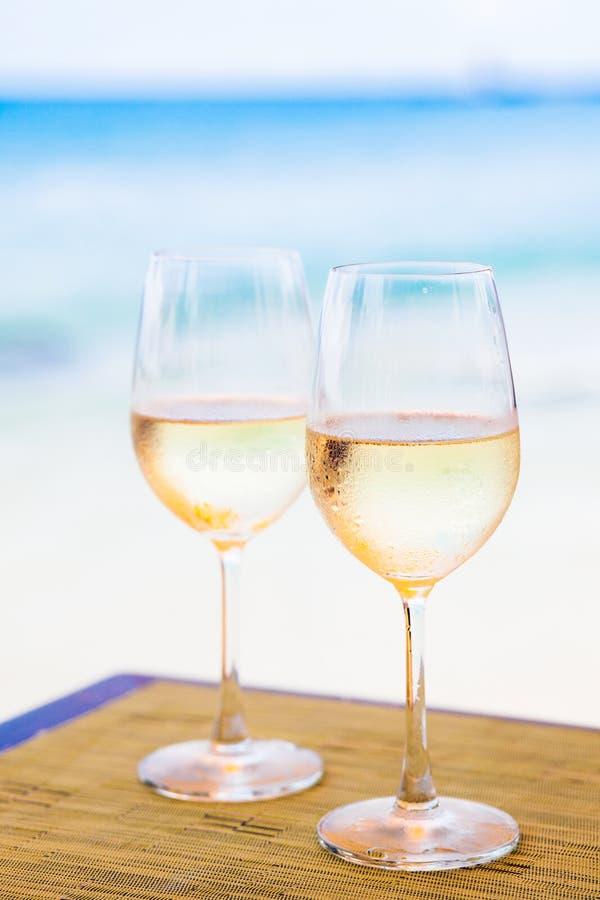 Deux verres de vin blanc effrayant sur la table près de la plage image libre de droits
