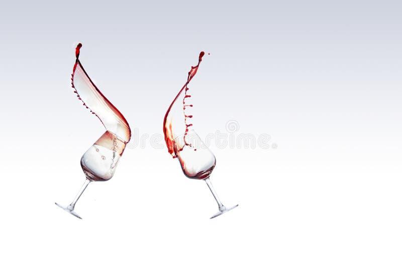 Deux verres de vin rouge avec du vin éclaboussant hors d'un de verre, d'isolement au-dessus du fond blanc photographie stock libre de droits