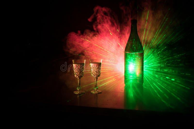 Deux verres de vodka avec la bouteille sur le club brumeux foncé dénomment le fond avec multi rougeoyant des lumières (laser, Sto image stock