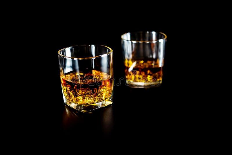 Deux verres de whiskey ou de whiskey avec de la glace sur le fond noir image libre de droits