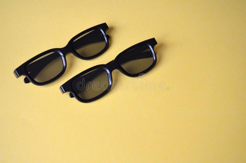 Deux verres en plastique noirs sur un fond jaune Lunettes de soleil, verres 3D pour le cinéma photo stock