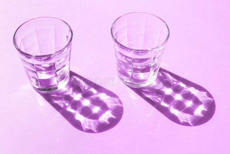 Deux verres en verre transparents sur le fond pourpre et ombres de eux avec les dessins intéressants photographie stock libre de droits