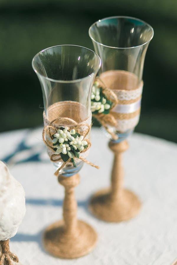 Deux verres les épousant de champagne décorés de la ficelle et des fleurs se tenant sur la table photos libres de droits