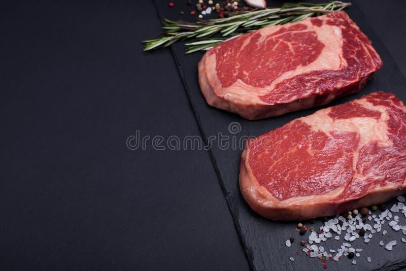 Deux viande de marbre crue fraîche, bifteck noir de ribeye d'Angus avec des épices sur un fond en pierre foncé image stock