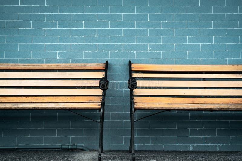 Deux vides banc en bois sur le fond vert de mur de briques Attente de quelqu'un pour remplir compl?tement chaise en bois vide Ban photo libre de droits