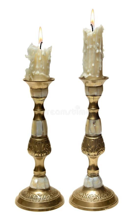 Deux vieilles bougies brûlantes dans des chandeliers d'or image stock