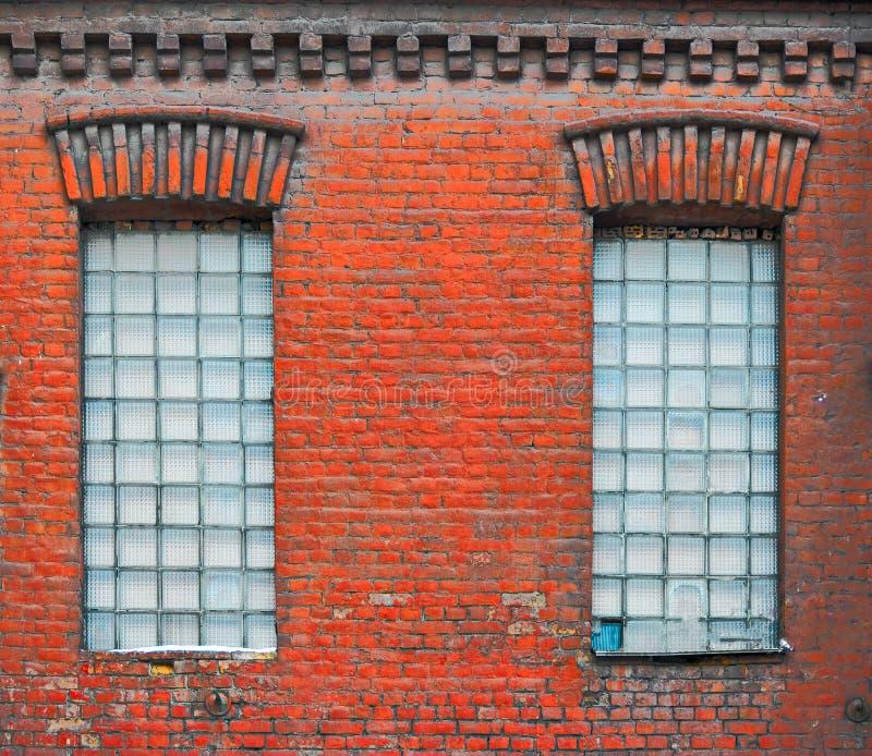 Deux vieilles fenêtres avec les blocs en verre carrés dans vieux porté en bas du bâtiment d'usine photo libre de droits