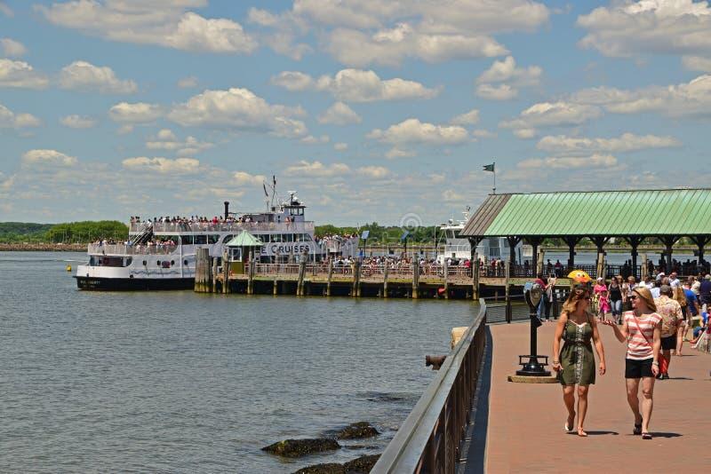 Deux visiteurs apprécient le jour tandis que d'autres visiteurs font la queue chez Liberty Island pour des croisières de statue à photos stock