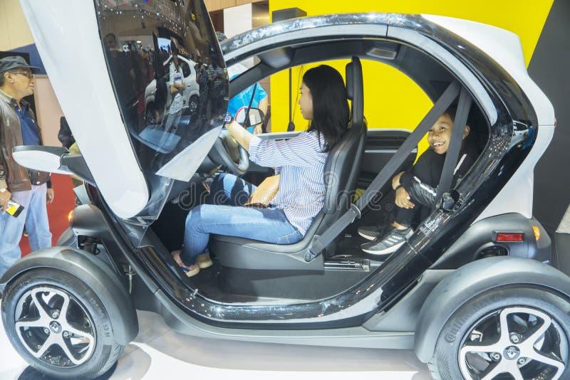 Deux visiteurs examinant la voiture de Renault Twizy photo stock