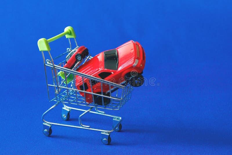 Deux voitures rouges dans un chariot d'un supermarché, un grand différent des autres sur le changement image stock