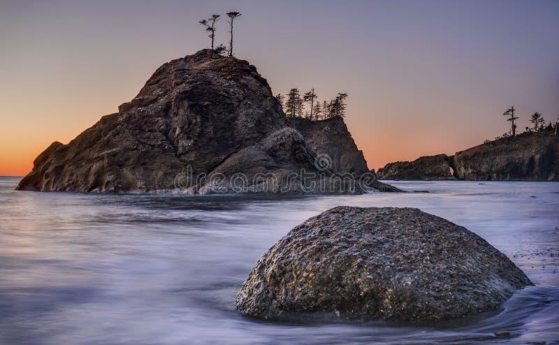 Deuxièmes piles de mer de plage au coucher du soleil photo libre de droits