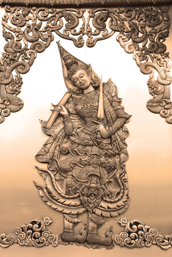 A Deva relief art work in sepia tone. The beautiful emboss art on the wall of wat in Thailand show a deva or a fairy in Thailand traditional royalty free stock photos
