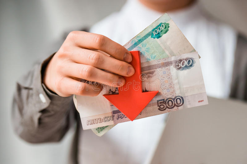 Devaluation. Business person holds roubles and red arrow. Devaluation of the Russian rouble royalty free stock photography