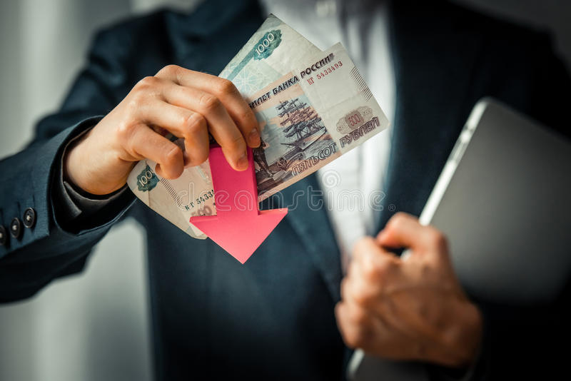 Devaluation. Business person holds roubles and red arrow. Devaluation of the Russian rouble stock photography