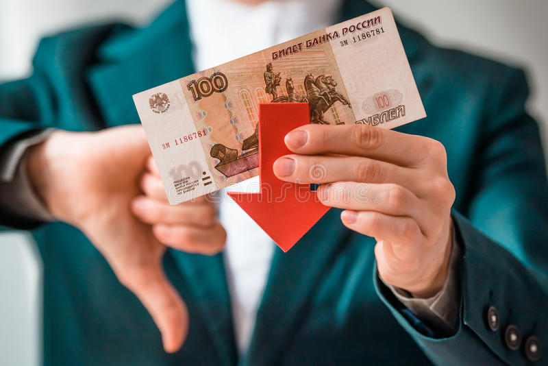 Devaluation. Business person holds roubles and red arrow and shows thumb down. Devaluation of the Russian rouble. Toned picture royalty free stock photos