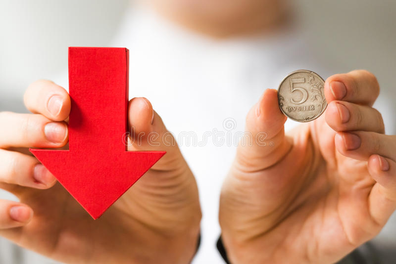Devaluation. Businessman holds roubles and red arrow. Devaluation of the Russian rouble royalty free stock images