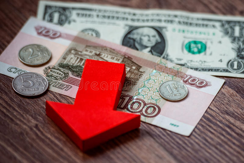 Devaluation. Coins and banknotes of russian roubles on us dollar bill. Devaluation of the Russian rouble royalty free stock image