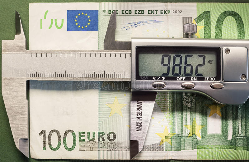 Devaluation. Conceptual composition representing money devaluation, symbolically showed with sliding calliper measuring a hundred euros royalty free stock photography