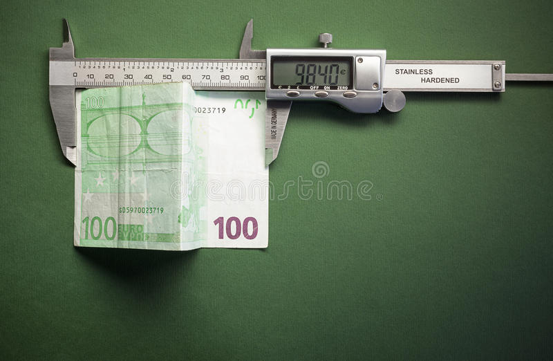 Devaluation. Conceptual composition representing money devaluation, symbolically showed with sliding calliper measuring a hundred euros royalty free stock photos