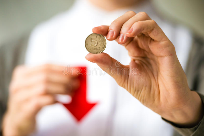 Devaluation. Person holds rouble coin and red arrow. Devaluation of the Russian rouble stock images