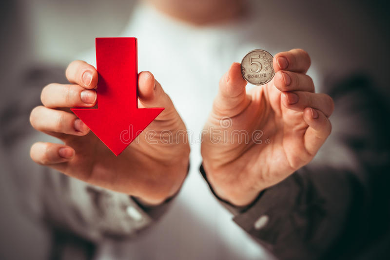Devaluation. Person holds rouble coin and red arrow. Devaluation of the Russian rouble. Toned picture royalty free stock photo