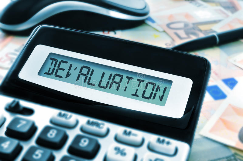 Devaluation. Word devaluation on the display of a calculator with euro bills in the background royalty free stock photography