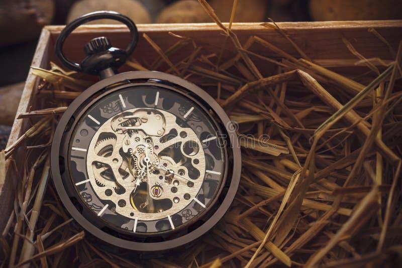 Devanadera del reloj de bolsillo en la paja natural del trigo en una caja de madera fotografía de archivo
