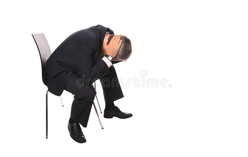 Devastated businessman. Devastated middle aged businessman with head in hands sat on chair, isolated on white background royalty free stock images