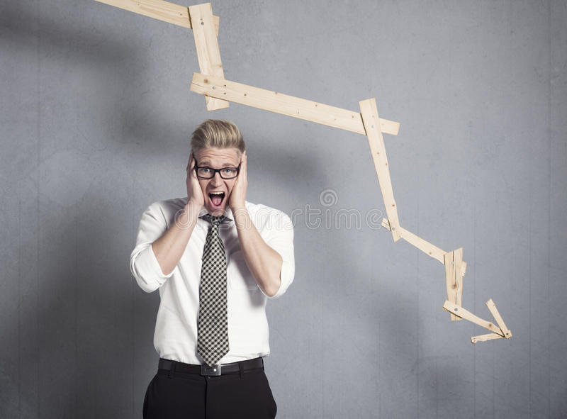 Devastated businessman shouting in front of graph pointing down.