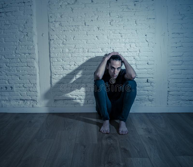 Desperate lonely teenager man suffering from depression sitting alone on floor at home. Devastated depressed millennial man crying sad feeling hurt suffering stock image
