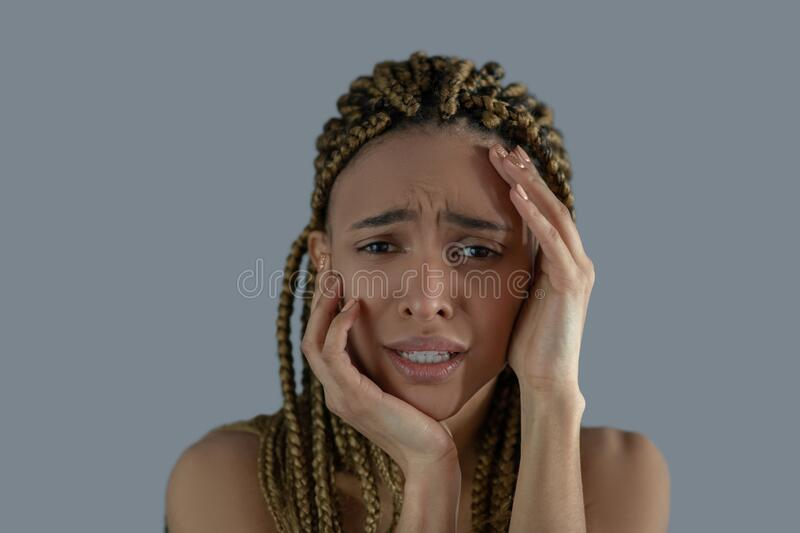 Devastated young African American holding her face with her hands, frowning with pain royalty free stock image