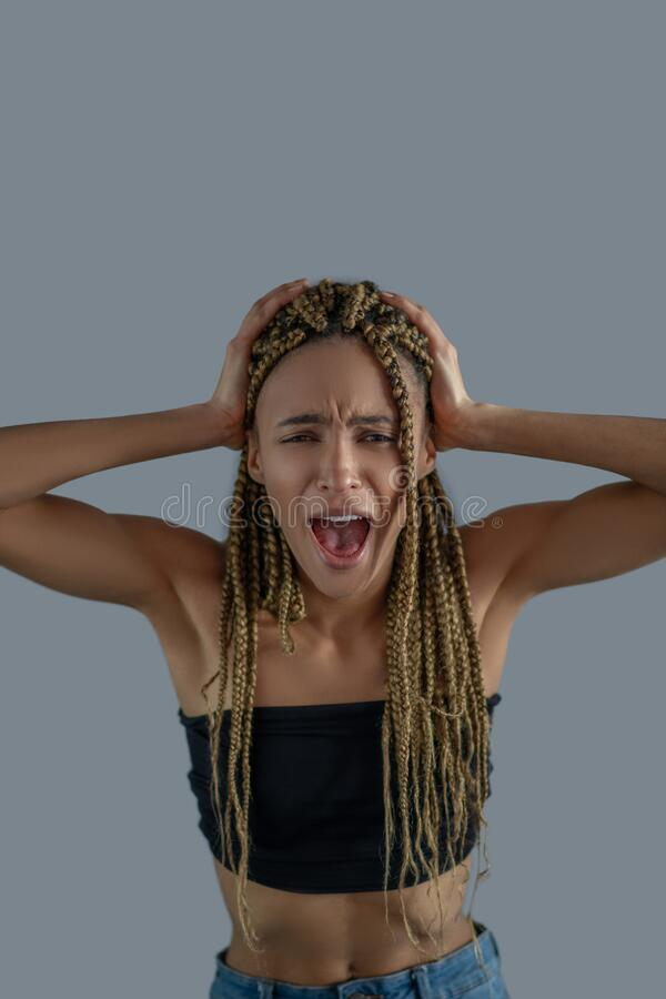 Devastated young African American holding her head in hands, screaming royalty free stock photos