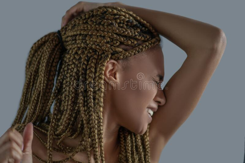 Devastated young African American holding her head with one arm, frowning with pain royalty free stock photo