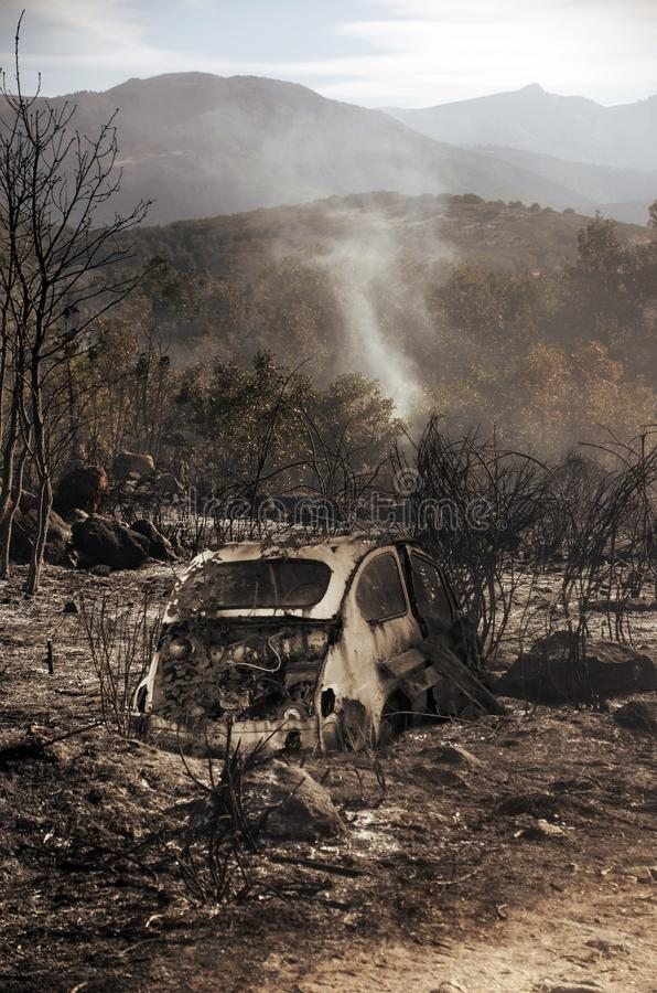 Devastation due to Summer Fire. Landscape of fields and mounts burned in summer, due to the carelessness of people. An old car has been burned there stock photo