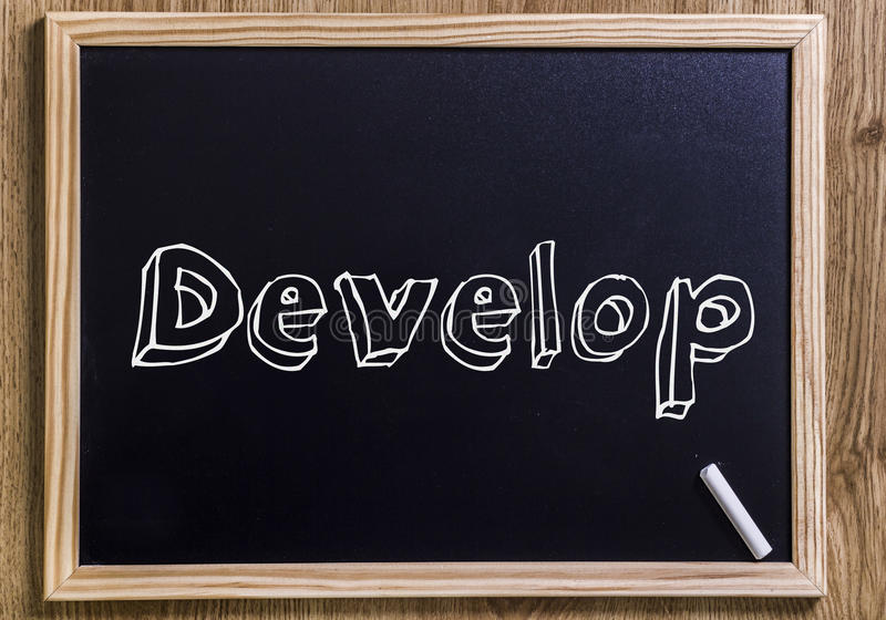 Develop. New chalkboard with 3D outlined text - on wood royalty free stock photography
