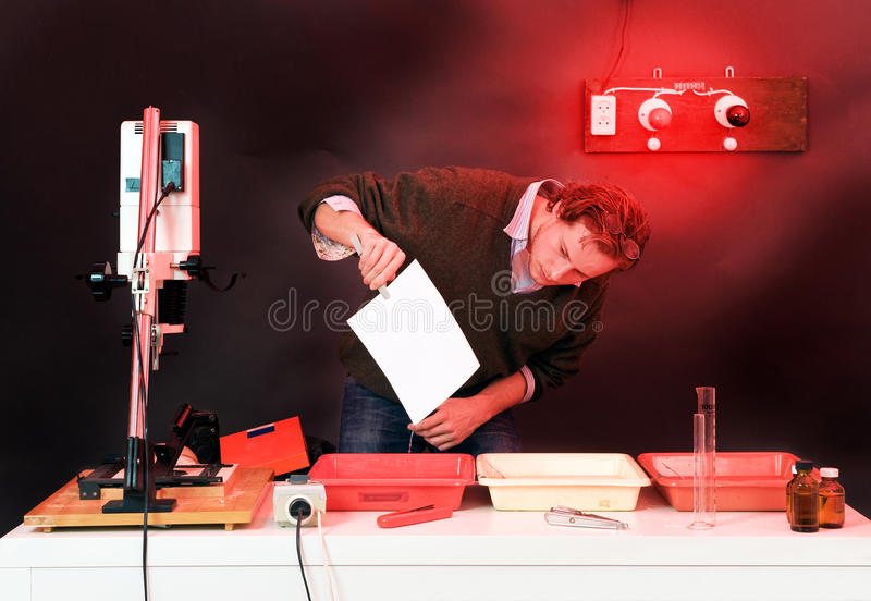 Developing. Photographer at work in a dark room, developing analogue prints stock photo