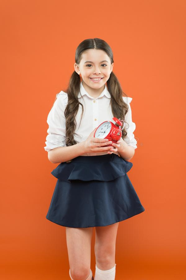 Developing discipline. Time for break and relax. Vacation time. Elementary school day bell schedule. Schooltime concept. Avoid being late. Schoolgirl hold stock image