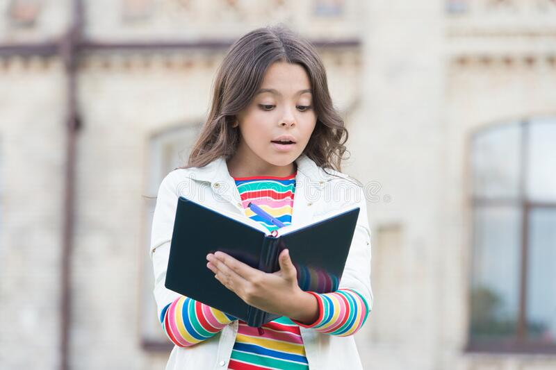 Developing her reading skills. Little girl read book outdoor. Small kid enjoy reading day. Adorable bibliophile. Child. Imagination. Home reading. School and royalty free stock photo