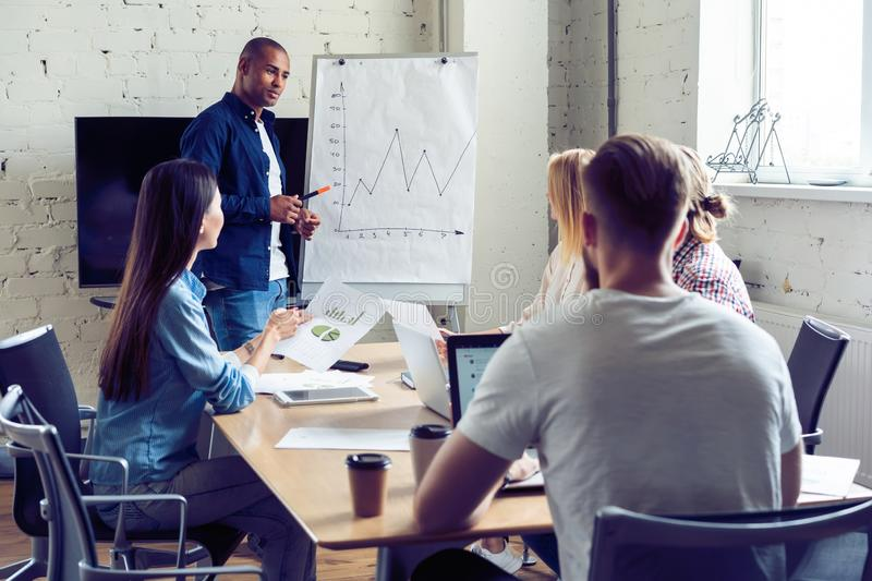 Developing new strategy. Modern young man conducting a business presentation in the board room. royalty free stock image