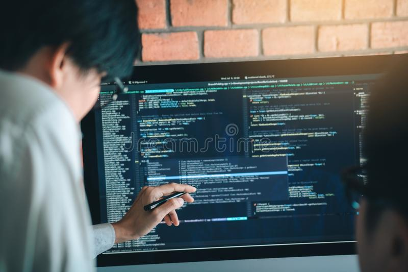 Developing programming and coding technology working in a software engineers developing applications together in office stock photography